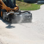 skid-steer-pick-up-broom-attachment-sweeping dirt virnig-mfg
